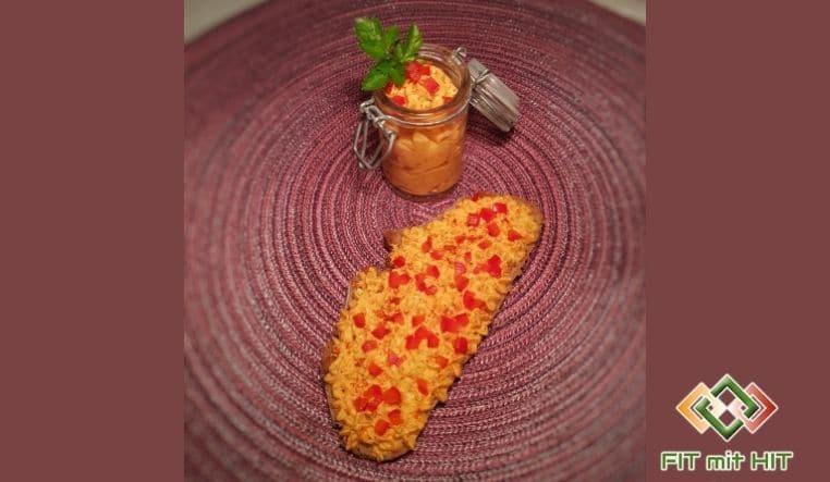 Scheibe Brot mit Ajvar-Aufstrich und Paprikawürfel
